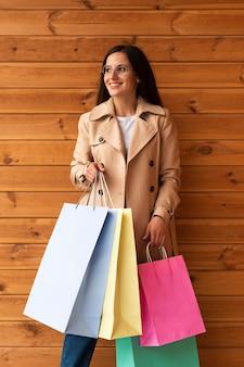 Mujer sonriente posando sosteniendo bolsas de la compra.