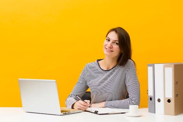 Mujer sonriente posando en su escritorio mientras escribe algo