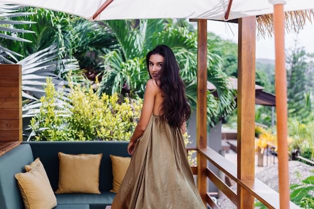 Mujer sonriente positiva bastante europea en vestido de vuelo de verano a la luz natural del día en la terraza de la villa disfrutando de hermosas vacaciones, sofá al aire libre con almohadas en tropical