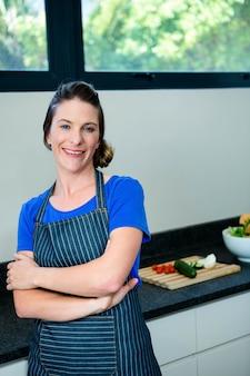 Mujer sonriente preparando verduras para la cena en una tabla de cortar de madera