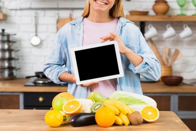 Mujer sonriente de primer plano con maqueta de tableta