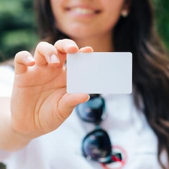 Mujer sonriente del primer que sostiene una maqueta de la tarjeta
