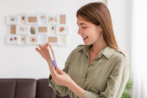Mujer sonriente con prueba de embarazo