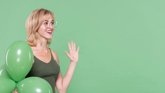 Mujer sonriente que agita su mano