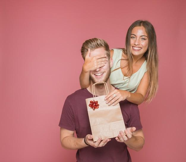 La mujer sonriente que cierra los ojos del novio que dan el panier de papel