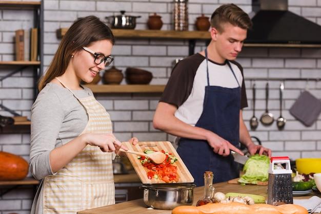 Mujer sonriente que cocina la ensalada con el novio