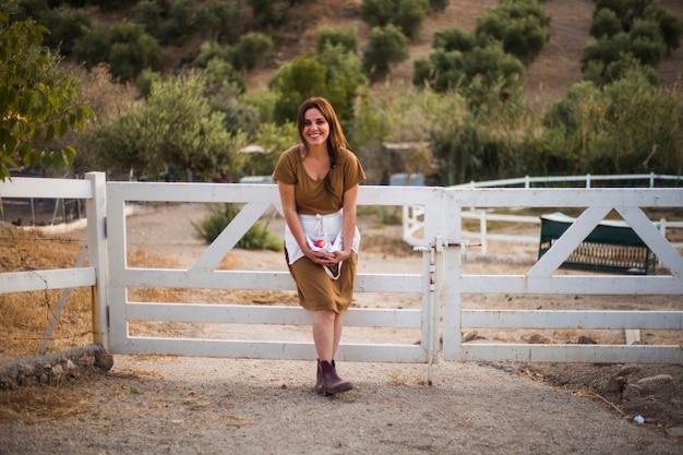 Mujer sonriente que se coloca cerca de la puerta que sostiene la manzana roja en delantal