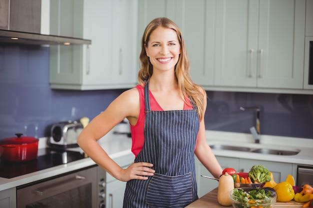 Mujer sonriente que se coloca en una cocina