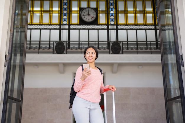 Mujer sonriente que se coloca con la maleta en pasillo de la estación