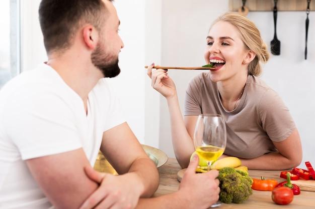 Mujer sonriente que come con su hombre