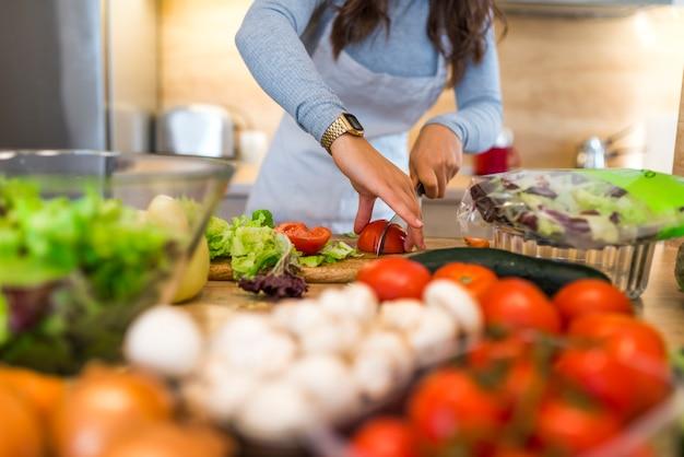 Mujer sonriente que corta un tomate en su cocina