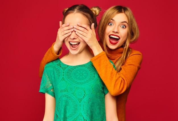 Mujer sonriente que cubre los ojos con las manos a su amiga