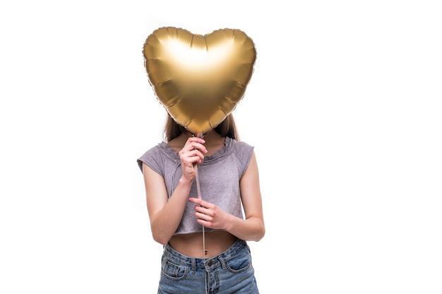 Mujer sonriente que cubre su ojo con globo en forma de corazón.