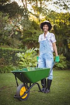 Mujer sonriente que empuja la carretilla en el jardín