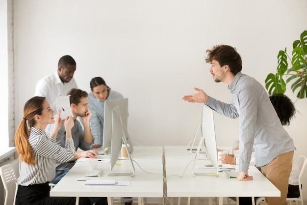 Mujer sonriente que explica el papeleo corporativo a un nuevo empleado en la oficina