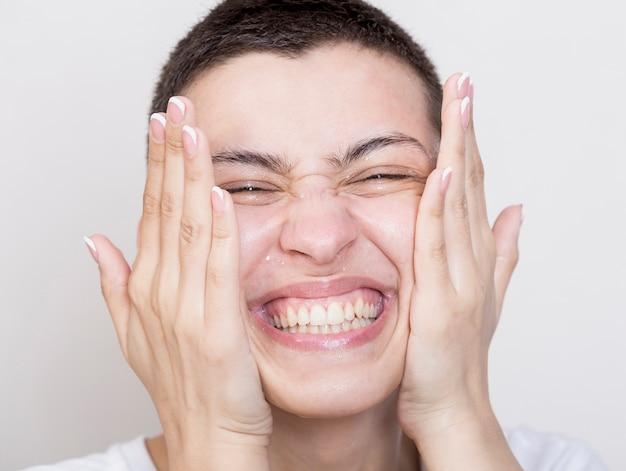 Mujer sonriente que limpia su primer de la cara
