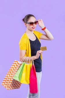 Mujer sonriente que lleva el bolso de compras colorido con sostener la tarjeta del oro en el papel pintado púrpura