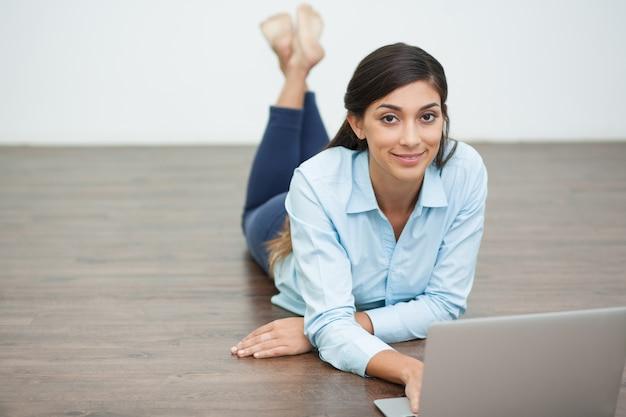 Mujer sonriente que miente en suelo y trabajar en la computadora portátil