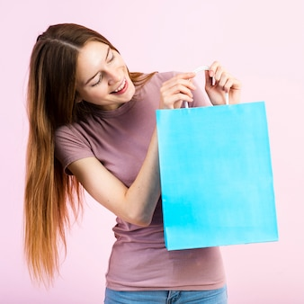 Mujer sonriente que mira la bolsa de papel azul