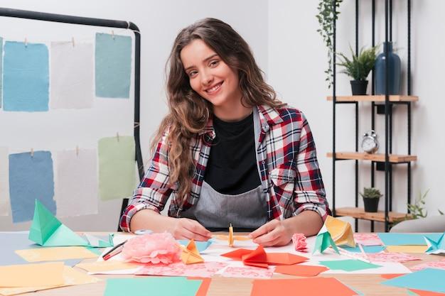 Mujer sonriente que mira la cámara mientras que hace el arte