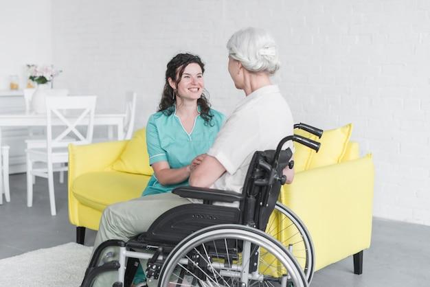 Mujer sonriente que mira a la mujer mayor que se sienta en la silla de rueda