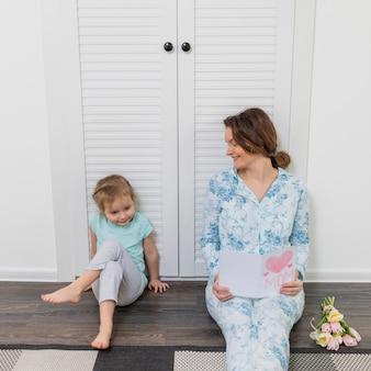Mujer sonriente que mira a su hija sentada en un piso de madera con una tarjeta de felicitación