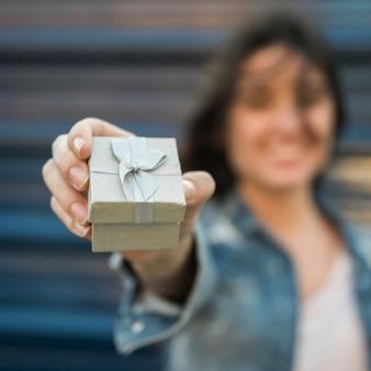 Mujer sonriente que muestra la actual caja