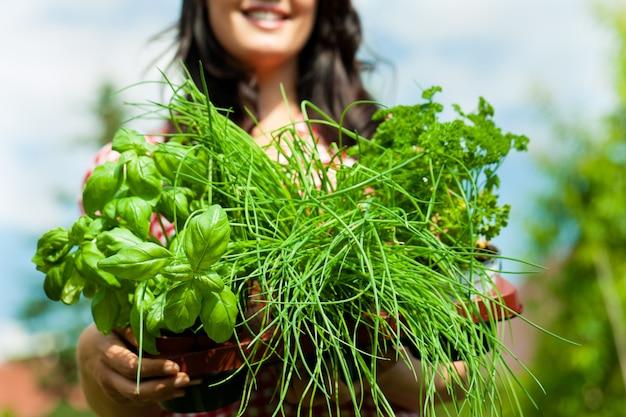 Mujer sonriente que muestra algunas hierbas en macetas a la cámara