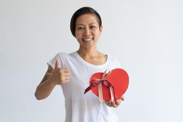Mujer sonriente que muestra la caja y el pulgar en forma de corazón de regalo para arriba