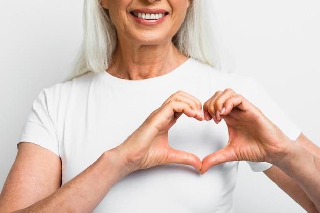 Mujer sonriente que muestra el corazón con las manos