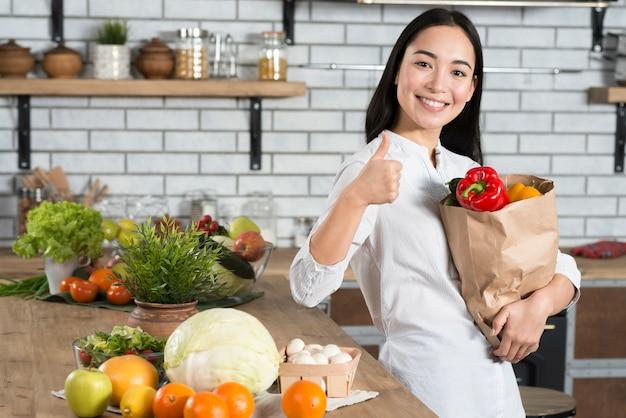 Mujer sonriente que muestra el pulgar encima de la muestra mientras sostiene el bolso marrón de la tienda de comestibles