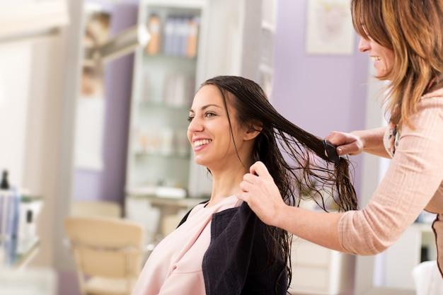 Mujer sonriente que peina el pelo después del lavado