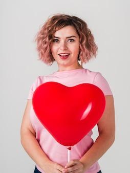 Mujer sonriente que presenta con el globo