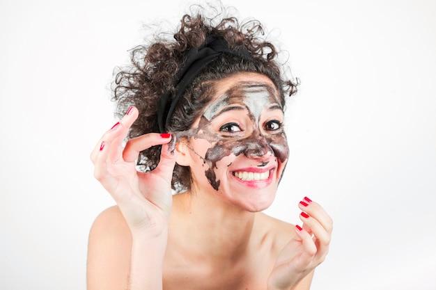 Mujer sonriente que quita la máscara purificadora de su cara sobre fondo blanco