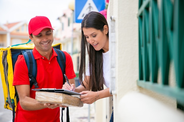 Mujer sonriente que recibe la caja del paquete del repartidor. cartero con caja de cartón y hermosa clienta poniendo firma en el portapapeles para confirmar la recepción. servicio de entrega y concepto de correo.