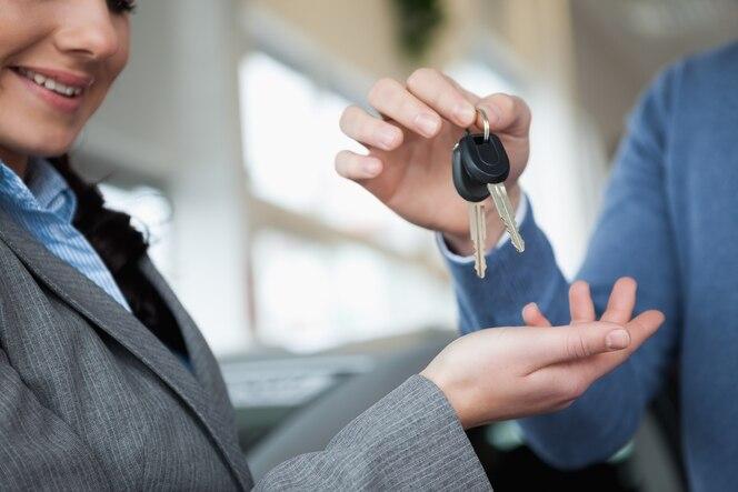Mujer sonriente que recibe llaves de una mano en una tienda de coches
