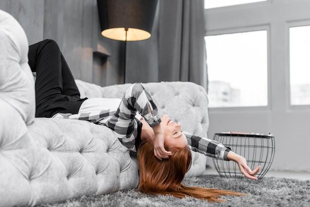 Mujer sonriente que se relaja en el sofá