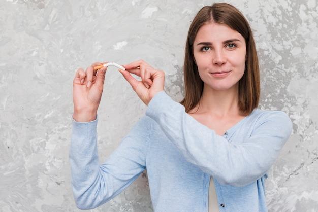 Mujer sonriente que rompe el cigarrillo delante de la pared resistida