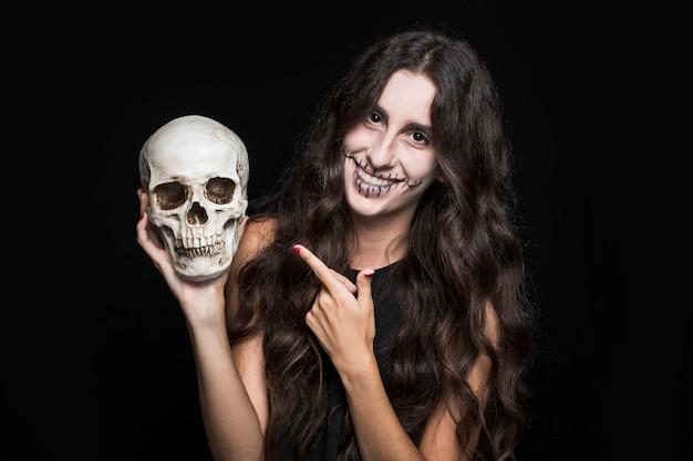 Mujer sonriente que señala en el cráneo