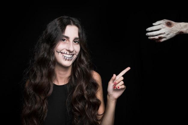 Mujer sonriente que señala en la mano muerta