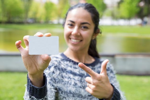 Mujer sonriente que señala en la tarjeta de visita en blanco en parque de la ciudad