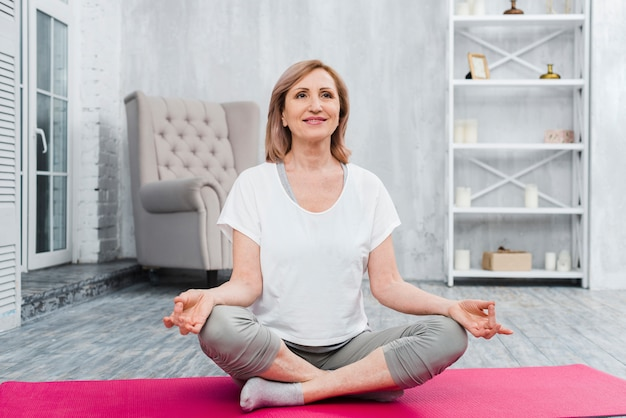 Mujer sonriente que se sienta en la estera de la yoga practicando yoga en casa