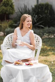 Mujer sonriente que se sienta en silla en el jardín que revuelve el café en taza