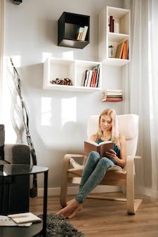 Mujer sonriente que se sienta en silla y que lee el libro en casa