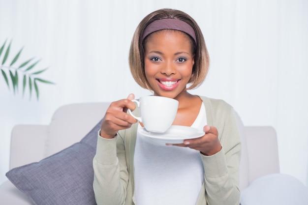Mujer sonriente que se sienta en el sofá que sostiene el café