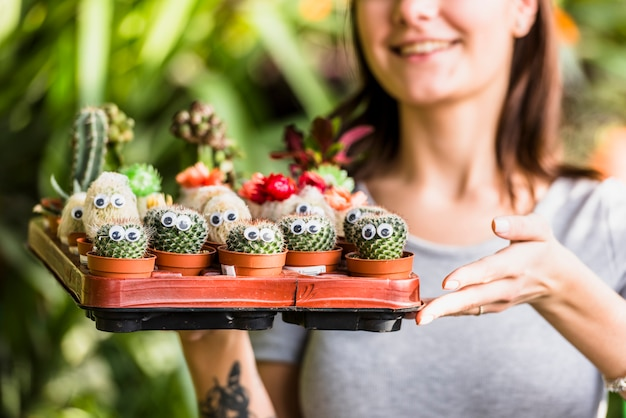 Mujer sonriente que sostiene la bandeja con cactus verdes