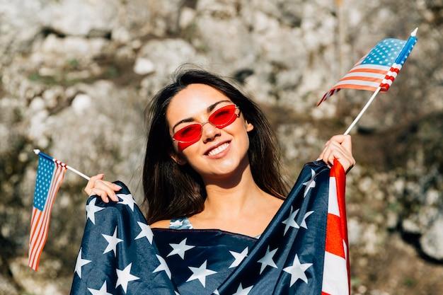 Mujer sonriente que sostiene banderas americanas en luz del sol
