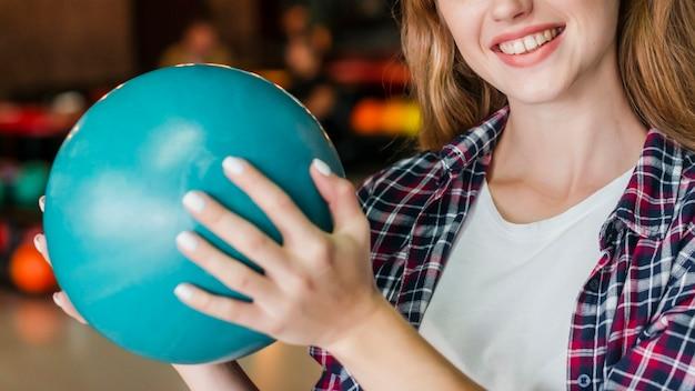 Mujer sonriente que sostiene una bola de bolos turquesa