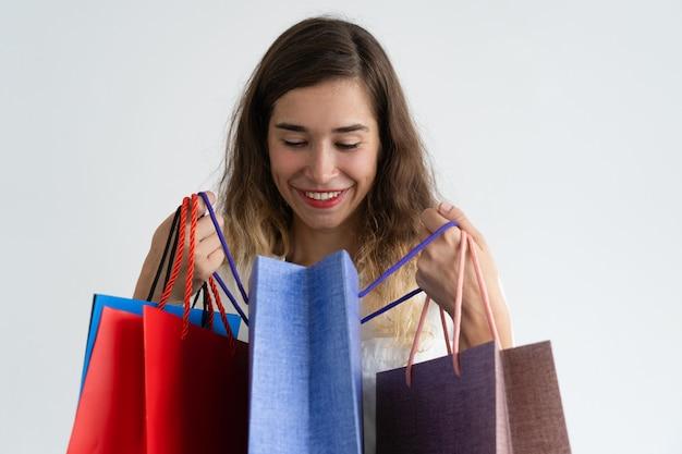 Mujer sonriente que sostiene bolsos de compras y que mira furtivamente en uno de ellos.