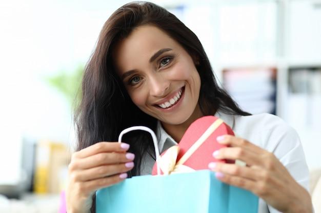 Mujer sonriente que sostiene la caja en forma de corazón